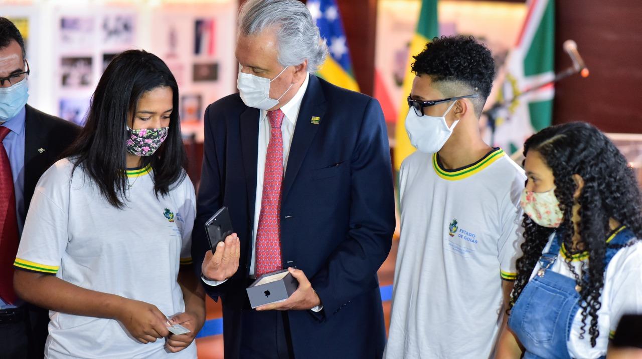 O governador Ronaldo Caiado entrega smartphone a Thauana Guadalupe Lima Barbosa, de 16 anos, em meio a outros estudantes que também serão beneficiados