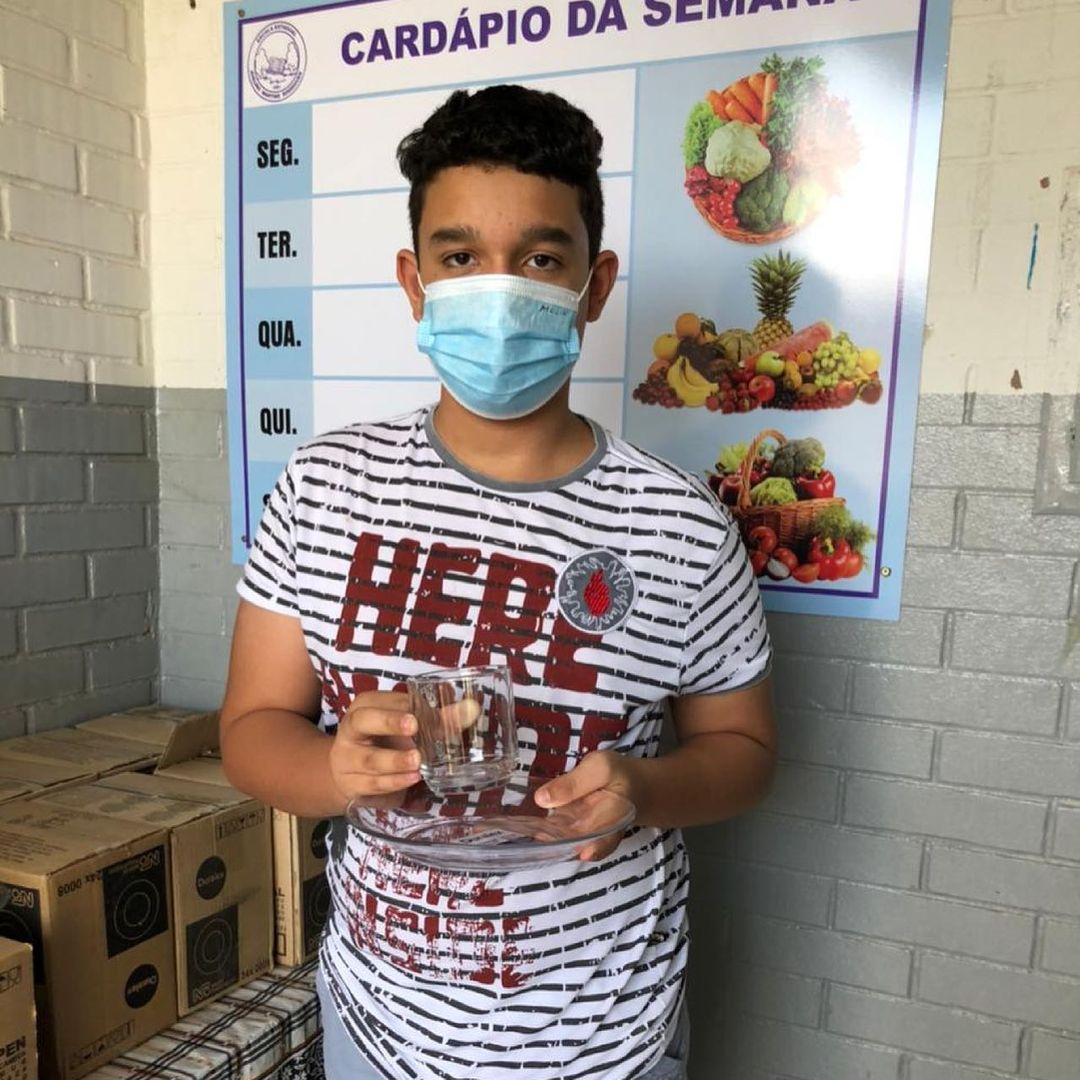 Estudante da Escola Estadual Avelino Martins Rodrigues segurando caneca e prato de vidro